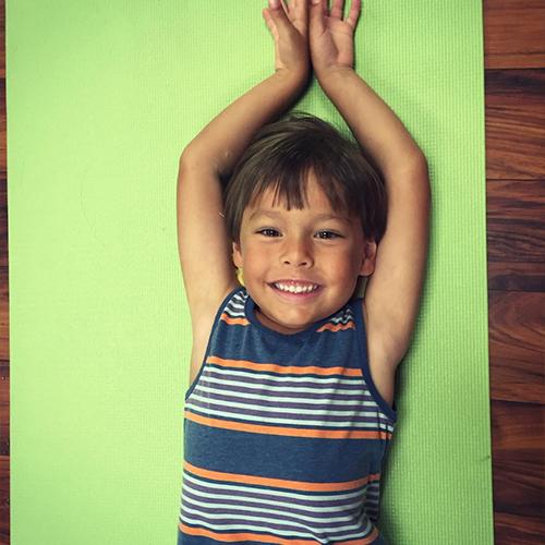 Little boy laying on yoga mat