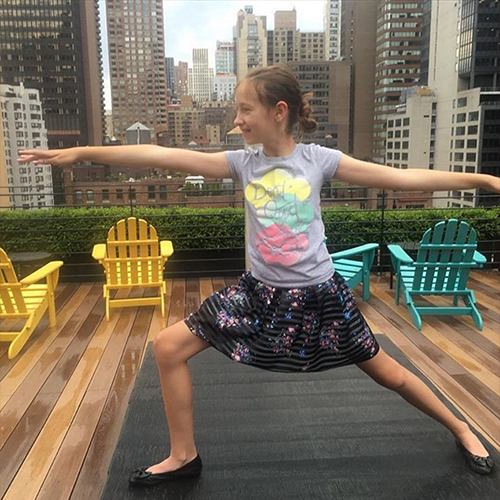 Little girl in warrior 2 pose on rooftop